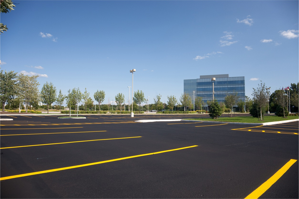 A picture of an empty parking lot with a building in the background.